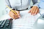 Bild zeigt Hand, die mit Taschenrechner und Stift Aktienkurse bewertet
