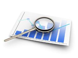 Eine Lupe liegt auf einem Blatt mit Aktienkursen