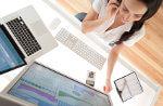 Bild zeigt eine Frau, die am Computer mit Wertpapieren handelt