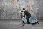 Bild zeigt Mann auf Schildkröte