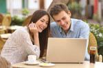 Paar vergleicht Online Broker am Laptop