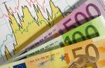 Bild zeigt Geldscheine vor Aktienkursen