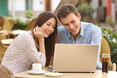 Junges Paar sitzt am Laptop und vergleicht Depots