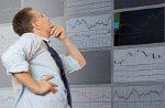 Bild zeigt einen Börsenmakler, der vor Börsenkursen steht und überlegt