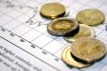 Bild zeigt Geldmünze und rapide fallende und steigende Kurse