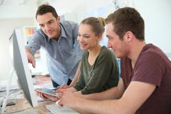 Eine Gruppe junger Menschen sitzt vor einem Rechner und diskutiert Anlagestrategien